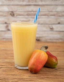 Succo di anacardi in un bicchiere con frutta sul tavolo di legno.