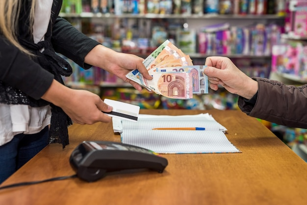 Il cassiere prende la banconota in euro dalla mano del consumatore Foto Premium