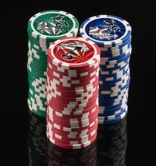 Chip del casinò su uno sfondo nero con riflesso il concetto di gioco d'azzardo e intrattenimento