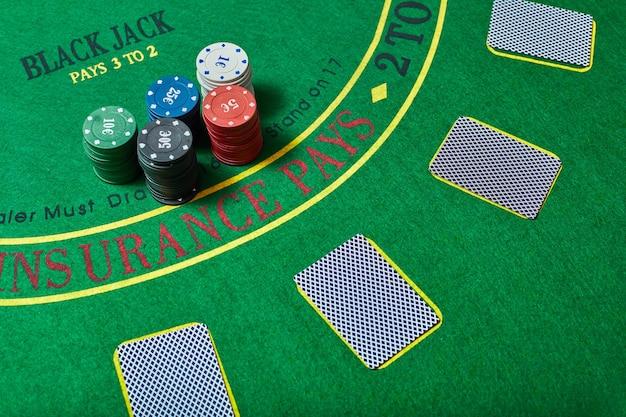 Fiches del casinò e mazzo di carte sdraiato sul tavolo del casinò verde, concetto di gioco di poker, vista dall'alto.