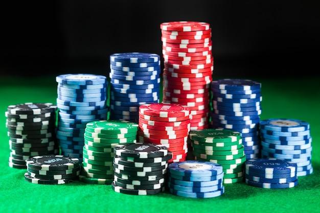 Di fiches del casinò sulla superficie del tavolo verde. concetto di gioco d'azzardo, fortuna, gioco e intrattenimento - da vicino