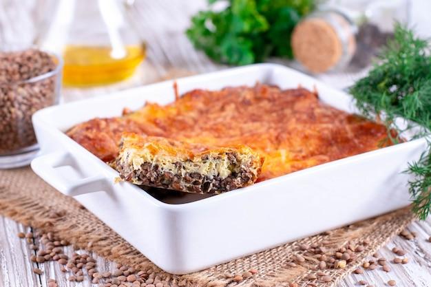 Casseruola con lenticchie, uova e formaggio in forma di ceramica