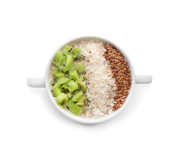 Casseruola con gustosa farina d'avena, semi di sesamo e kiwi su bianco