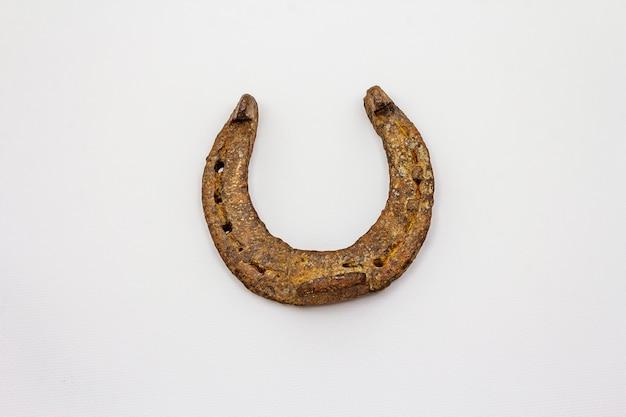 Ferro di cavallo del cavallo del metallo del ghisa isolato su fondo bianco