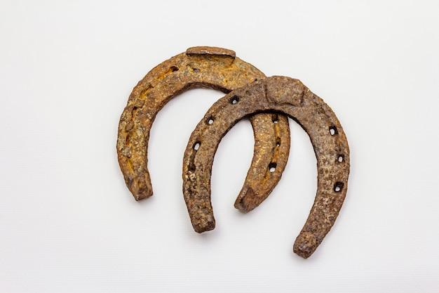 Ferri di cavallo del metallo del ghisa isolati su fondo bianco