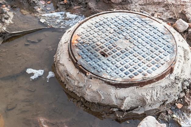 Un tombino fognario in ghisa circondato da una pozza d'acqua in un cantiere edile. costruzione di pozzi fognari.