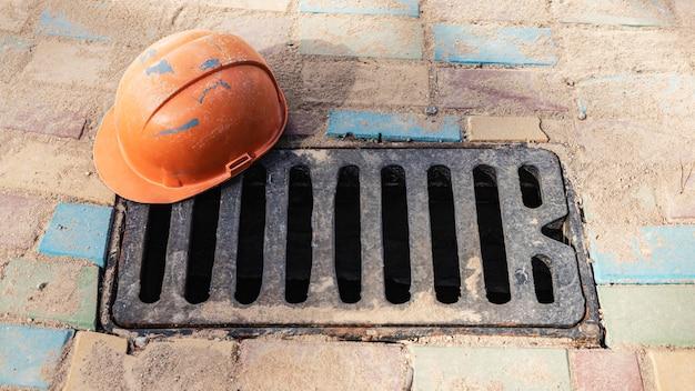 Un portello di drenaggio delle acque piovane in ghisa sul marciapiede con un casco da costruzione sdraiato su di esso. raccolta e drenaggio dell'acqua piovana dalla strada.