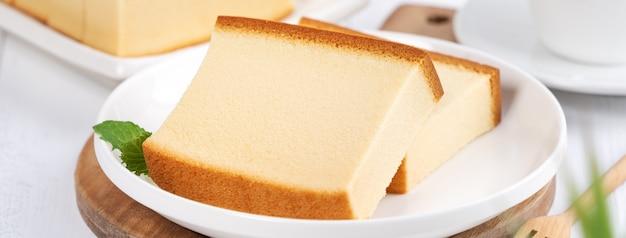 Castella (kasutera) - cibo delizioso delizioso pan di spagna affettato giapponese sul piatto bianco sul tavolo in legno bianco rustico, close up, concetto di design dello spazio della copia.