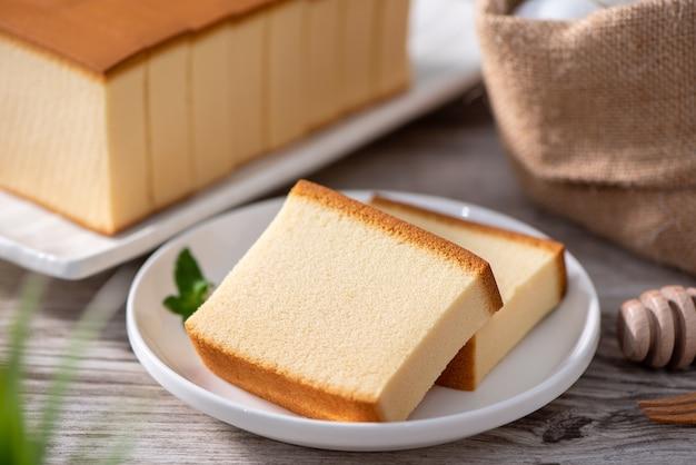 Castella (kasutera) - delizioso cibo giapponese a fette di pan di spagna su piatto bianco su tavola in legno rustico, primo piano, mangiare sano, copia spazio design.