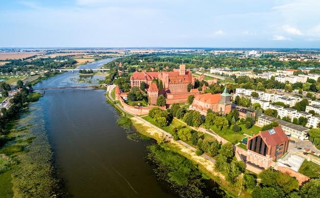Il castello dell'ordine teutonico a malbork sulla riva del fiume nogat. in polonia