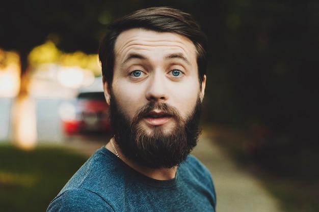 Casual uomo adulto con barba e baffi guardando sorpreso a porte chiuse su offuscata