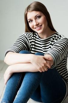 Bellezza casuale. bella giovane donna in abiti a righe seduta sul pavimento e sorridente