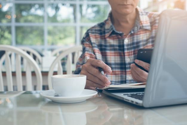 Uomo d'affari casual che lavora al computer portatile nella caffetteria