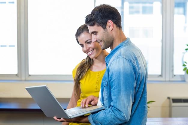 Soci commerciali casuali che esaminano computer portatile