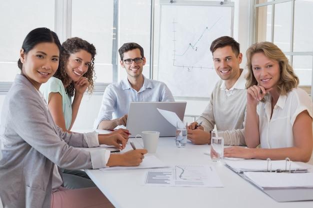 Squadra casuale di affari che ha una riunione che sorride alla macchina fotografica