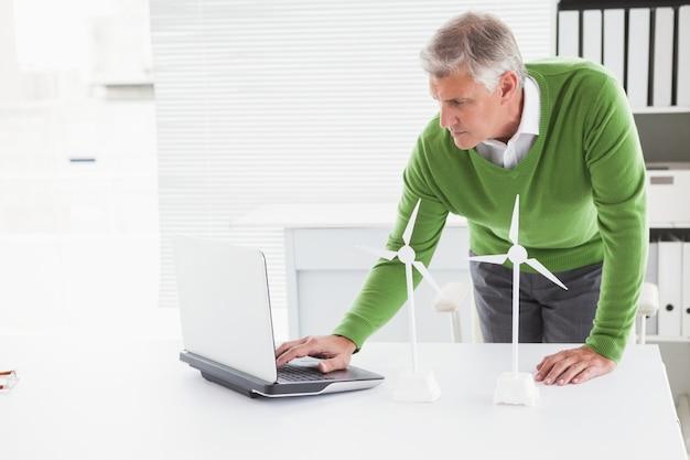 Uomo d'affari casuale che esamina le turbine eoliche di modello