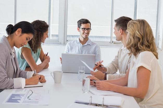 Uomo d'affari casuale che parla con squadra nel corso della riunione