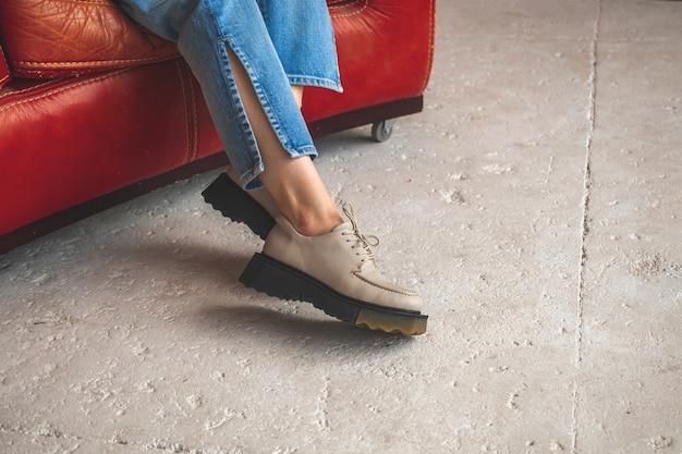 Moda casual con scarpe urbane su gambe femminili in jeans denim. studio girato su una vecchia sedia in pelle rossa e una foto di sfondo in cemento