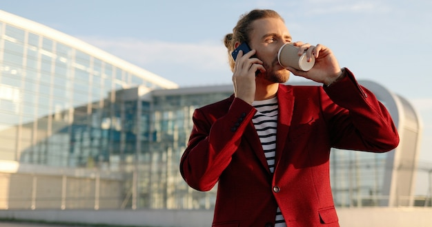 Maschio bello felice casuale in giacca rossa in piedi all'aperto, sorseggiando una bevanda calda e parlando al cellulare. in un grande edificio moderno in vetro. uomo caucasico che beve caffè, sorridente e parlando al telefono cellulare
