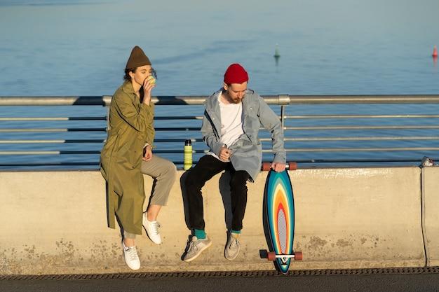 Casual hipsters ragazzo e ragazza alla data insieme bevono tè seduti sul ponte sul fiume al tramonto sun