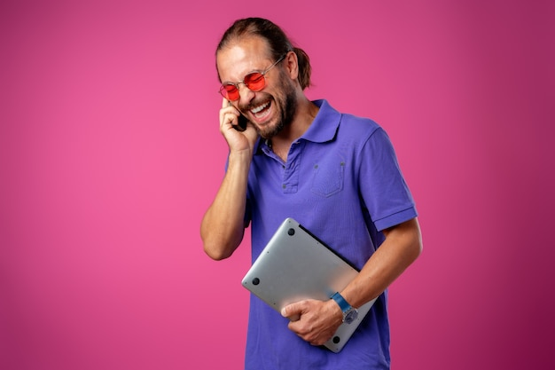 Uomo casuale in vetri che stanno con il computer portatile contro il rosa