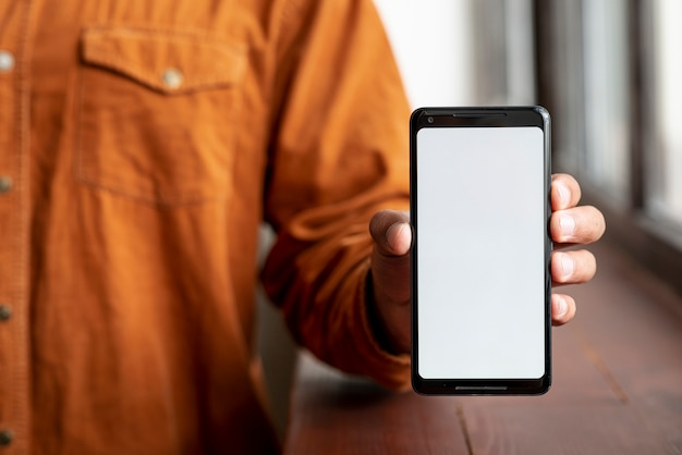 Uomo casuale che mostra il suo telefono cellulare Foto Premium