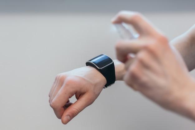 Uomo casual che spruzza alcol antisettico sul suo smartwatch