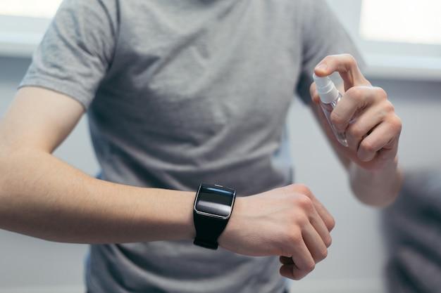 Uomo casual che spruzza disinfettante sul suo smartwatch