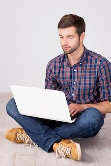 Uomo casuale che lavora al computer portatile. bel giovane che lavora al computer portatile mentre è seduto sul pavimento di legno duro