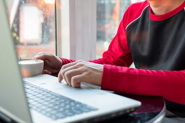Uomo casuale che lavora con il computer portatile e che beve caffè nella caffetteria