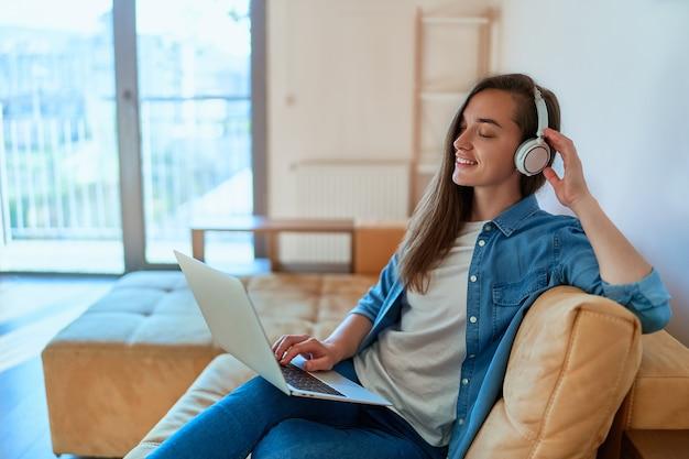 Casual smart modern sorridente ragazza millenaria amante della musica con gli occhi chiusi utilizzando cuffie wireless e laptop, godendosi l'ascolto di musica durante il relax sul divano di casa
