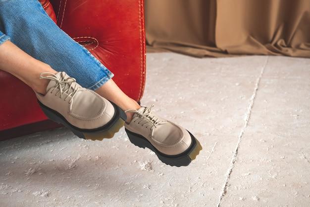 Scarpe da ginnastica casual sulle gambe della ragazza adolescente in jeans denim. concetto di moda urbana e di strada. adolescente seduto su una vecchia sedia in pelle rossa, foto di sfondo in cemento