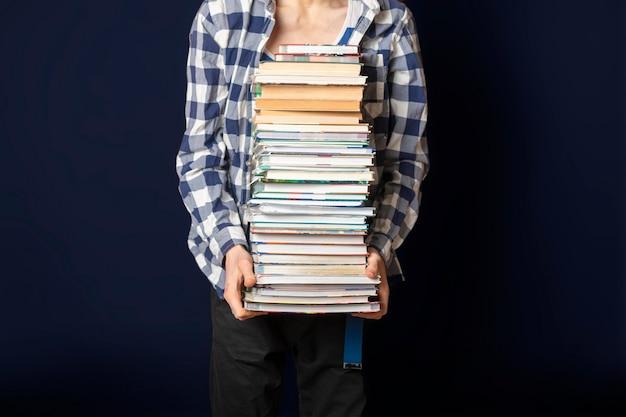 Lo studente casuale porta un'enorme pila di libri su sfondo scuro f