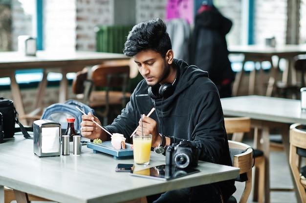 Giovane uomo asiatico casuale ed alla moda con le cuffie al caffè che mangia i sushi
