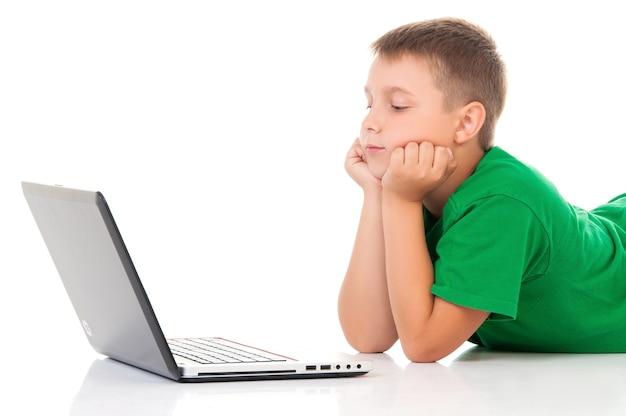 Adolescente casual in maglietta verde brillante con laptop su sfondo bianco