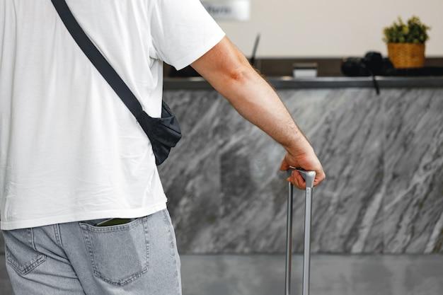 Casual uomo irriconoscibile in piedi con la valigia bagagli si chiuda