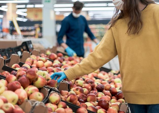 Donna casuale in abbigliamento protettivo che compra frutta durante il periodo di quarantena. concetto di sicurezza