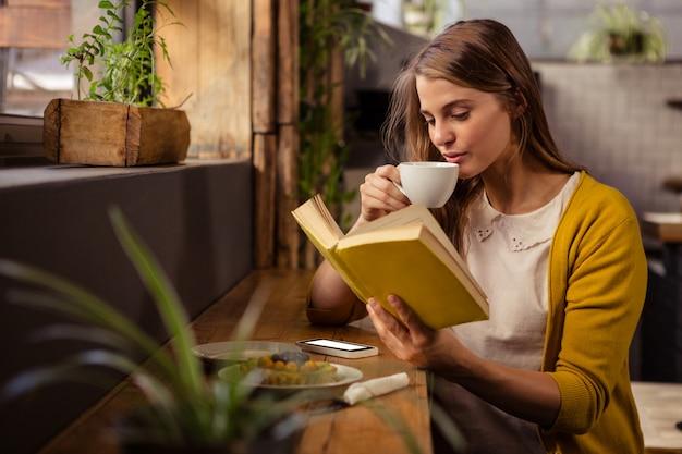 Donna casuale che legge un libro mentre bevendo