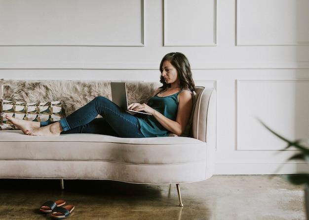 Donna casuale che lavora sul suo laptop mentre è sdraiata sul divano