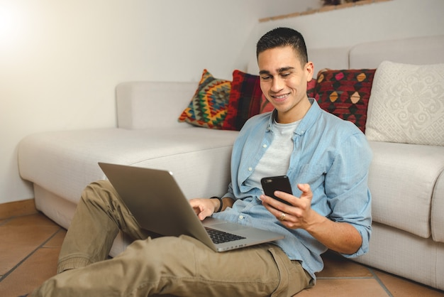 Casual giovane uomo a casa sorridente sul computer portatile tenendo lo smartphone.