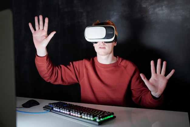 Giovane casual in cuffie vr seduto da scrivania davanti allo schermo del computer virtuale nell'oscurità