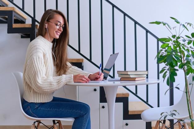 Giovane studentessa intelligente sorridente casuale in cuffie soddisfatta dell'apprendimento della lingua straniera. femmina che prende appunti al taccuino durante la visione di corsi video webinar. formazione online