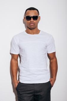 Casualmente bello. fiducioso giovane africano in occhiali da sole che si tiene per mano in tasca