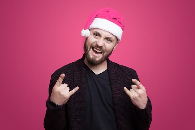 L'uomo barbuto di casuca sta gesticolando il segno del rock and roll mentre sorride su un muro rosa che porta il cappello della santa