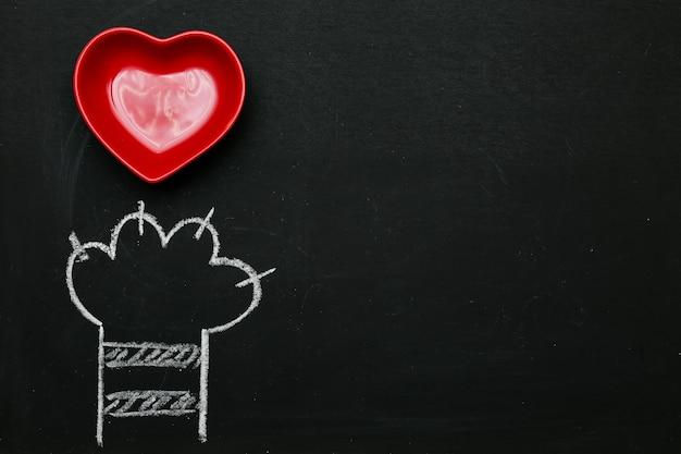 Cuore rosso della zampa di gatto disegnato in bianco su una lavagna nera
