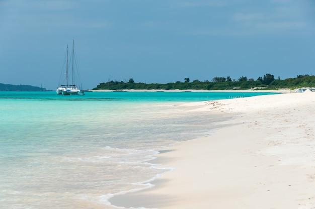 Catamarano attraccato in un meraviglioso mare verde smeraldo. spiaggia di sabbia bianca.