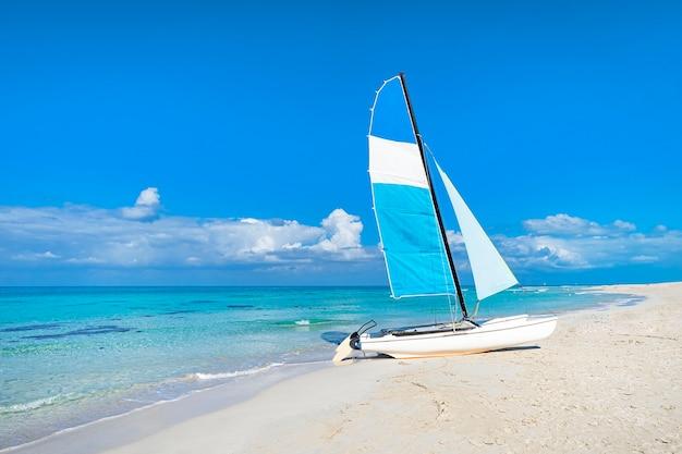 Catamarano sbarcato sulla bellissima spiaggia di varadero a cuba. attrazioni turistiche sulla costa caraibica. barca a vela sullo sfondo di limpide acque turchesi nel mare e nel cielo.