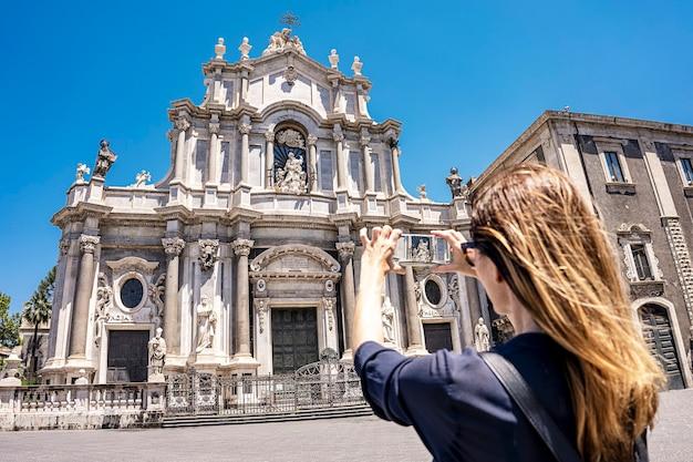 Catania, sicilia, piazza del duomo con il duomo di sant'agata, turista scatta una foto con lo smartphone in una giornata di sole estivo