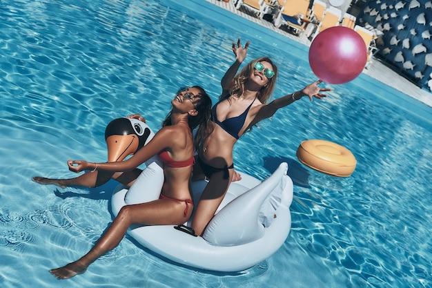 Prendere! vista dall'alto di una giovane donna giocosa in bikini che lancia una palla mentre galleggia su un grande cigno gonfiabile con la sua amica