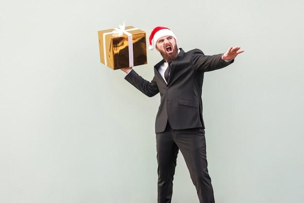 Prendi il tuo regalo! giovane adulto ben vestito uomo barbuto oscillato e vuole buttare via la tua confezione regalo, isolato su sfondo grigio. foto in studio